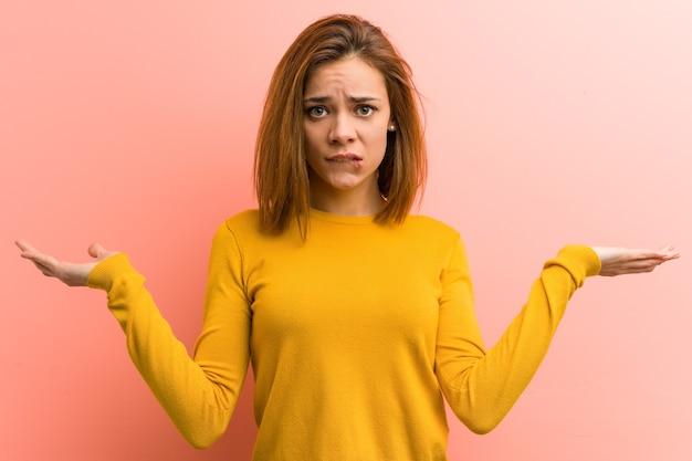 若いかなり若い女性は混乱し、コピースペースを保持するために彼女の手を上げることを疑っています。