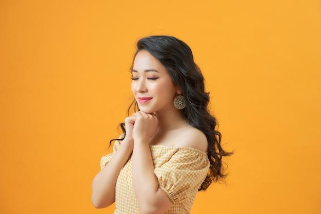 Молодая красивая молодая женщина держит руки под подбородком, закрывает глаза.