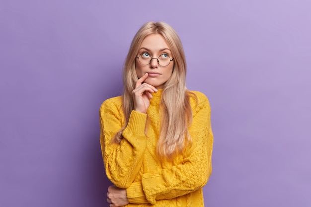 Young pretty young woman thinks of ideas concentrated above stands thoughtful and keeps hand on face stands in thoughtful pose wears round glasses yellow sweater