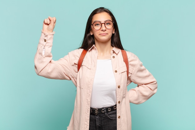 Young prewoman feeling serious, strong and rebellious, raising fist up, protesting or fighting for revolution. student concept