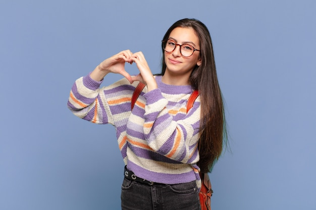 若いprewomanは笑顔で、幸せで、かわいくて、ロマンチックで、恋をしていて、両手でハートの形をしています。学生の概念