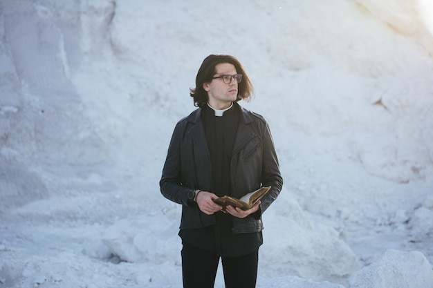 Портрет молодого священника снаружи на закате.