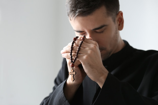 Young priest with rosary beads praying on light space