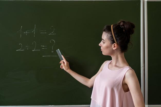 Молодая учительница начальных классов, написанная на доске один плюс один, концепция образования