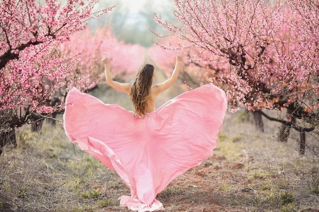 A young princess walks in a blooming garden. girl in a luxurious pink dress with a train. fashionable toning.