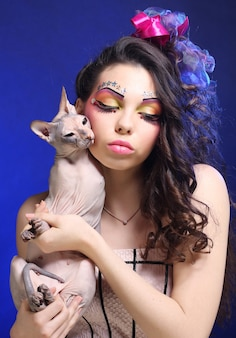 Young princess with sphynx cat. creative fantasy make-up.