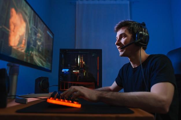 젊은 프로 게이머는 집에서 현대 컴퓨터에서 온라인 비디오 게임을 즐깁니다.