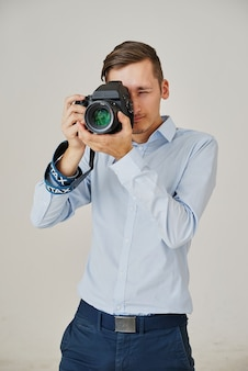 Young pro photographer with digital camera dslr and huge lens equipped studio, taking photos