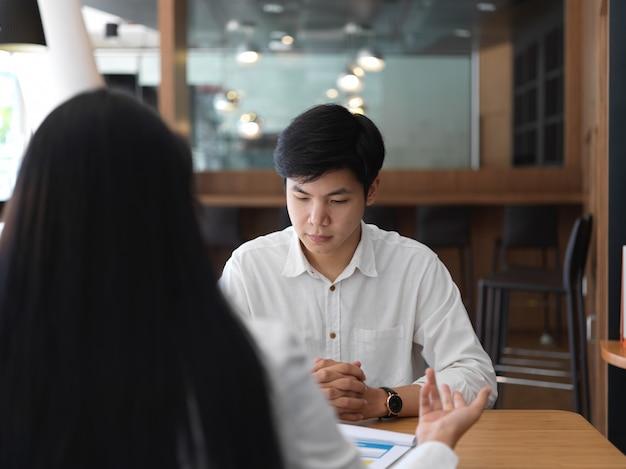 事務室で彼の同僚と彼のプロジェクトに取り組んでいる若い職業ビジネスマン