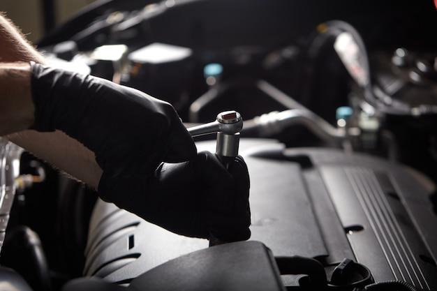 Молодой профессиональный автомеханик скручивает недостающий элемент внутри автомобиля с помощью гаечного ключа
