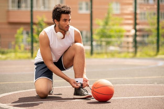 코트에서 게임을 준비하는 동안 운동화의 신발 끈을 묶는 젊은 프로 농구 선수