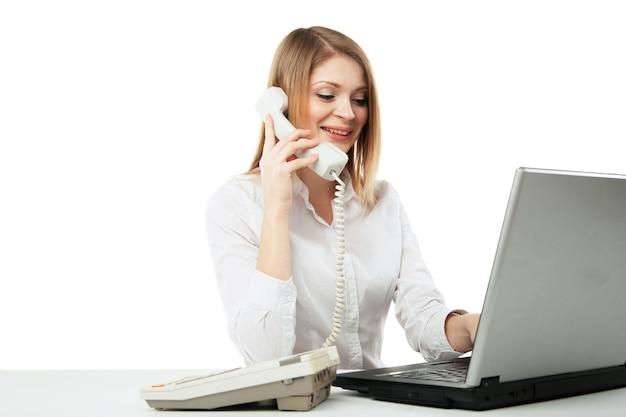 ノートパソコンを持って自分の机で働いて、白い背景の上で電話をかけたり、電話で会話しながら笑っている若いプロのビジネス女性。