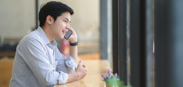 Young professional businessman speaking on the phone with his customer in modern office