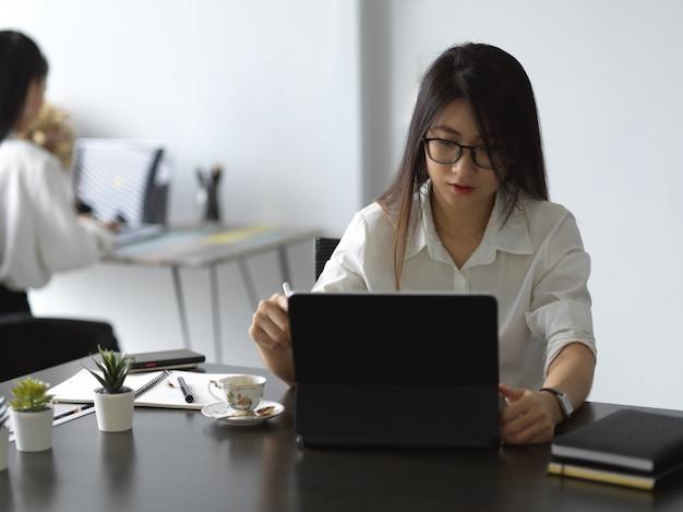Молодой профессиональный бизнесвумен концентрируется на своей работе во время работы с планшетом
