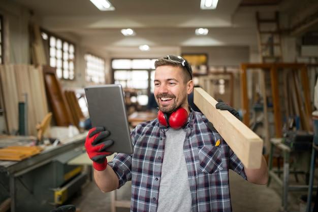 Молодой профессиональный плотник держит древесный материал и смотрит на планшет в столярной мастерской