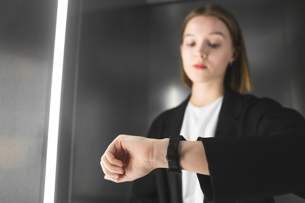 엘리베이터에서 그녀의 시계를 확인하는 젊은 전문가.