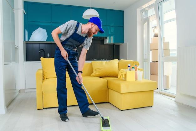 Молодой профессиональный уборщик моет пол. дворник корзина.