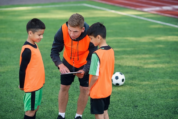 Young professional coach explains for kids the strategy of the game