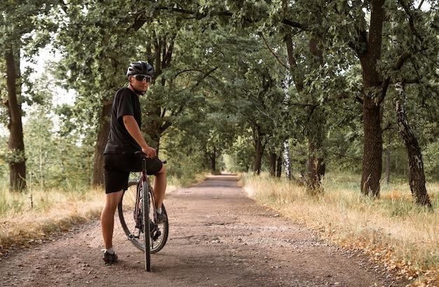 田舎道に立っている自転車とヘルメットと眼鏡の若いプロのサイクリスト。