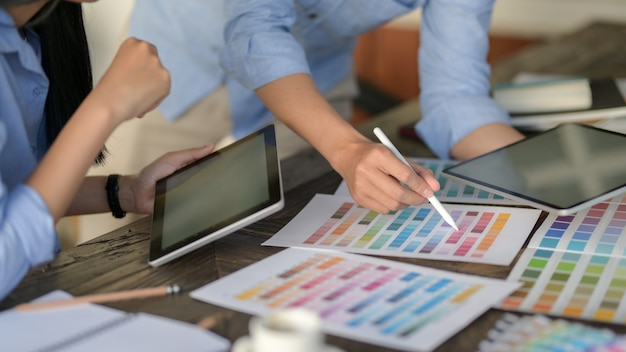 Young professional designer team using digital tablet while choosing colour on colour swatch