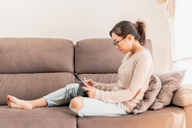 在宅勤務の若いプロのデジタルイラストレーターの女性。 Premium写真