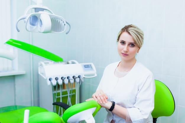 歯科用機器を備えた近代的なオフィスの若い専門医の歯科医。健康保険と無料の歯科治療の概念。補綴物とベニアの設置。