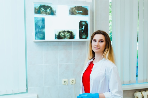 Young professional doctor dentist in a modern office with dental equipment. the concept of health insurance and free dental care. prosthetics and installation of veneers.