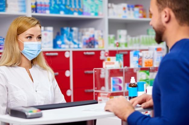 젊은 전문 약제사가 현대 약국에서 고객에게 약을 제공합니다.