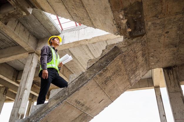 집 건물 건설 현장에서 손에 보호 헬멧과 청사진 종이에 젊은 전문 엔지니어 작업자