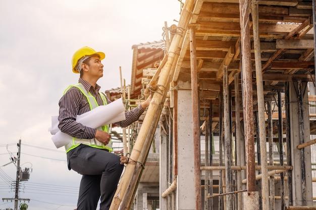 보호용 헬멧 및 청사진 종이에 젊은 전문 엔지니어 작업자 집 건물 건설 현장에서 사다리에서 작업 손에