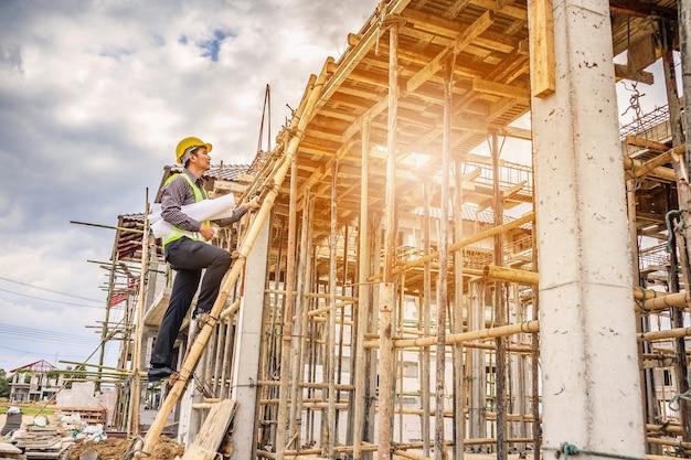 住宅建設現場ではしごに取り組んでいる手に保護ヘルメットと青写真の紙の若いプロのエンジニア労働者