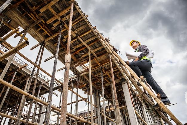家の建設現場で梯子に取り組んでいる一方で保護用のヘルメットと青写真の紙の若いプロのエンジニアワーカー