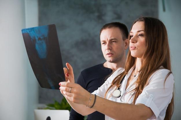 Молодая профессиональная женщина-врач показывает рентгеновский снимок черепа человека во время посещения пациента. концепция диагностики медицины здоровья
