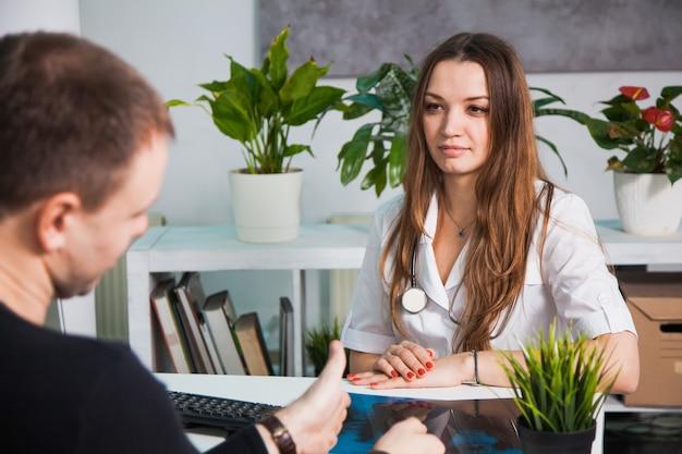 病院で患者と話している若い専門の女性医師。病人に相談し、処方箋を出す。健康医学診断の概念