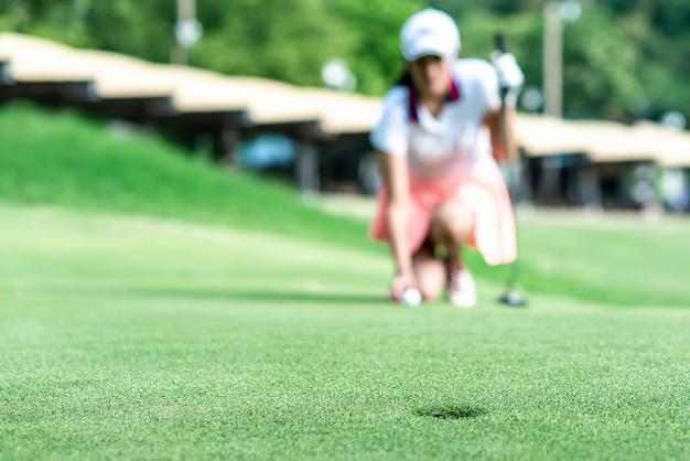 젊은 전문 여성 골프 선수 웅크 리고 총을 넣기 전에 녹색을 연구