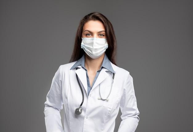 Молодой профессиональный практикующий врач в белом халате и защитной маске со стетоскопом на шее, глядя в камеру, стоя на сером фоне
