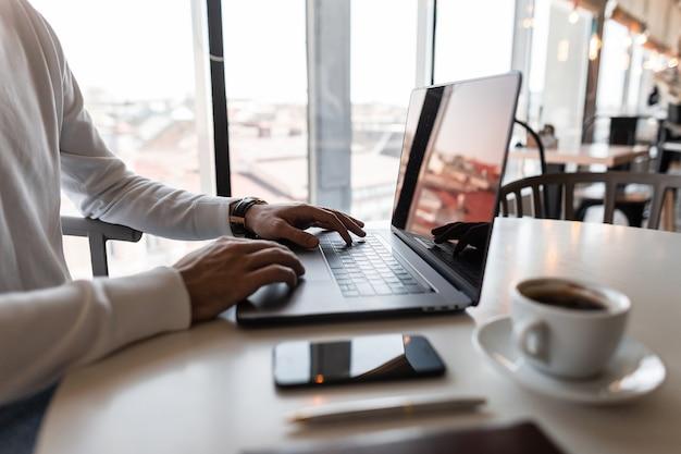 흰 셔츠에 젊은 전문 프리랜서 남자가 커피 한 잔이있는 카페의 테이블에 앉아있는 동안 자신의 노트북에서 작동합니다.