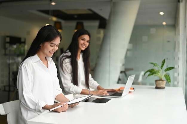 Команда молодых профессиональных графических дизайнеров обсуждает концепции вместе, используя ноутбук и планшет в офисе.