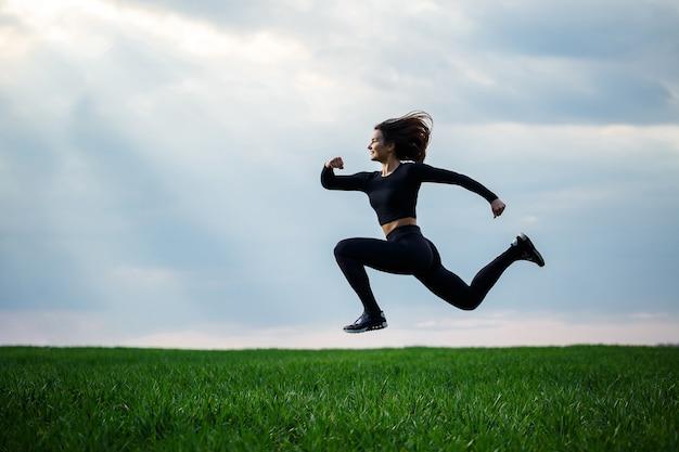 若いプロの体操選手は、青い空を背景に自然の中でジャンプしています。黒のトップと黒のレギンスの女の子アスリートはアクロバティックなエクササイズを行います