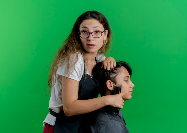 Young professional hairdresser woman in apron cutting hair with trimmer of man client, being surprised