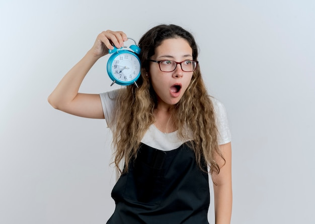 Giovane donna parrucchiere professionista in grembiule che tiene sveglia che osserva da parte essere sorpreso e stupito in piedi sopra il muro bianco