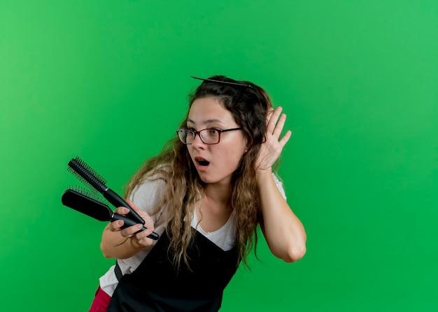 Giovane donna parrucchiere professionista in grembiule che tiene spazzole per capelli tenendo la mano vicino al suo orecchio cercando di ascoltare in piedi sopra la parete verde