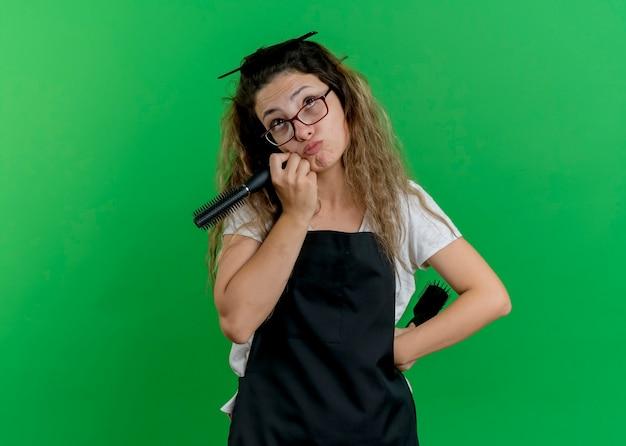 Giovane donna parrucchiere professionista in grembiule che tiene spazzole per capelli cercando perplessa