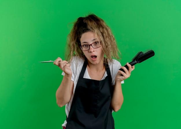 Giovane donna parrucchiere professionista in grembiule che tiene spazzole per capelli e forbici confusa e sorpresa