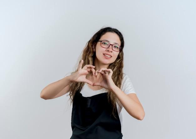 Giovane donna parrucchiere professionista in grembiule che fa il gesto del cuore con le dita sorridenti in piedi sopra il muro bianco