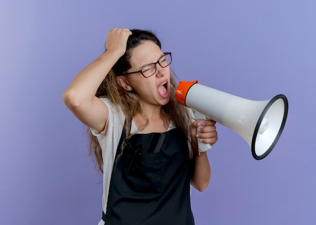 Young professional hairdresser woman in apron shouting to megaphone being frustrated