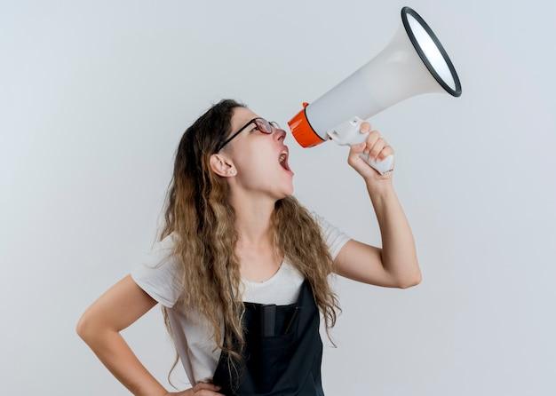 Donna giovane parrucchiere professionista in grembiule che grida al megafono ad alta voce in piedi sopra il muro bianco