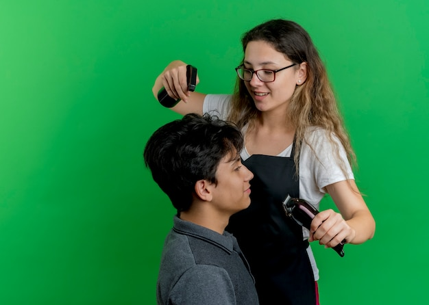 Young professional hairdresser woman in apron sprinkling water on hair of man client using spray before haircut