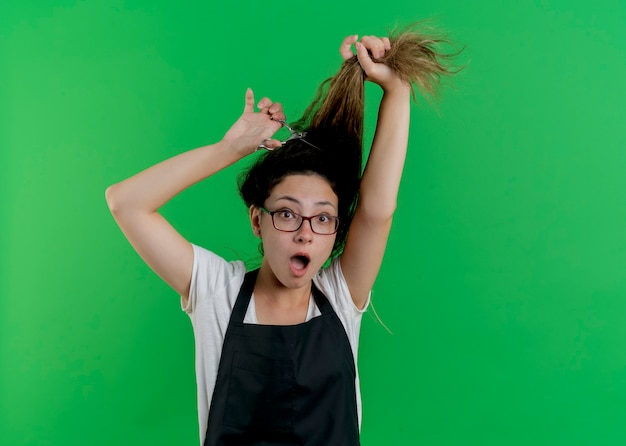 앞치마 칫솔질에 젊은 전문 미용사 여자가 그녀의 머리를하고 녹색 벽 위에 서 놀란