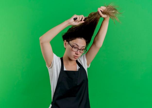 緑の壁の上に立ってエプロンブラッシングと彼女の髪をしている若いプロの美容師の女性